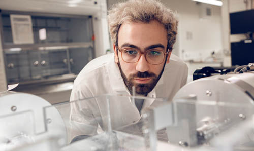 A male scientist inspects his experiment