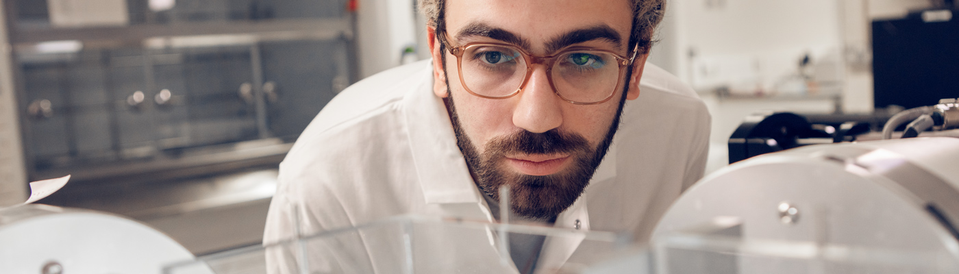 Student wearing white lab coat and glasses peering towards some equipment